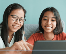 Mother and daughter smiling and looking at a laptop or tablet mother is pointing to the screen