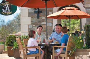 family of 4 eating and drinking at a table outdoors under umbrella on biltmore grounds at Cedric's Tavern in Antler Hill Village