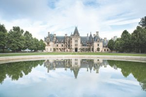 big Biltmore house in front of a pond with trees to the left and bright blue sky above