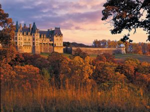 Fall at Biltmore house. Large house surrounded by trees and grass in red and orange hues and a light purple pink sky
