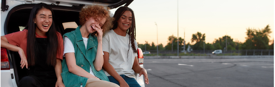 three woman laughing at the back of a car