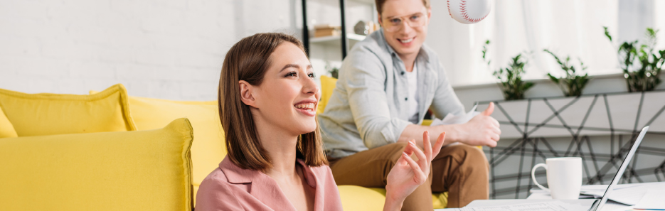 woman tossing baseball with man watching sitting in living room